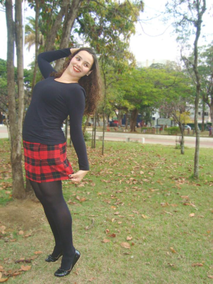 saia xadrez vermelha e preta, camiseta preta, sapatilha preta e meia calça preta no parque