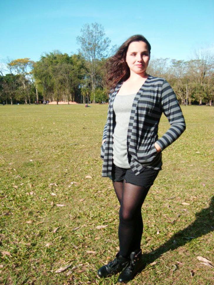 shorts com meia calça e botinha de cano curto, com cardigã listrado e blusa cinza básica