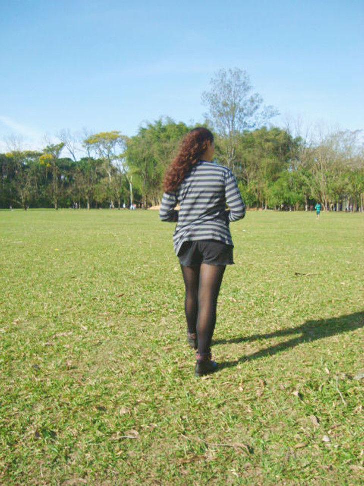 shorts preto com meia calça, bota de cano curto com detalhe xadrez e cardigã listrado de preto e cinza
