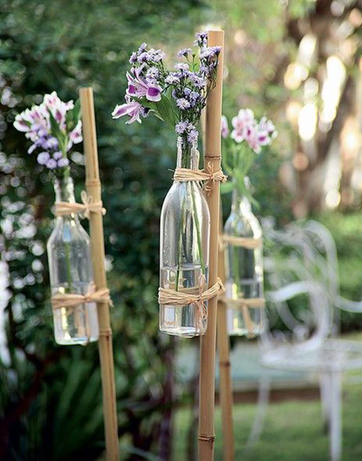arranjo de flores em garrafas de vidro para casamento