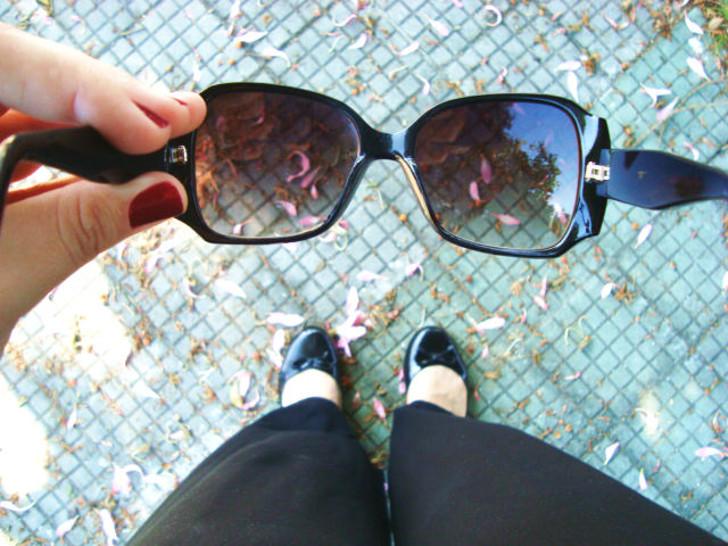 sapatilha preta e óculos de sol