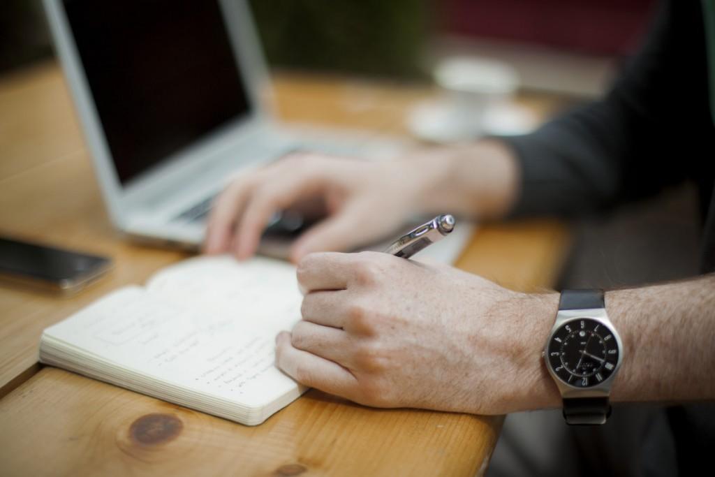 Pessoa com relógio mexendo no computador e fazendo anotações