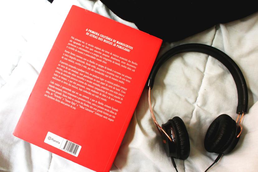 """Contracapa do livro """"As letras dos Beatles"""" em cima de uma cama com fone ao lado"""