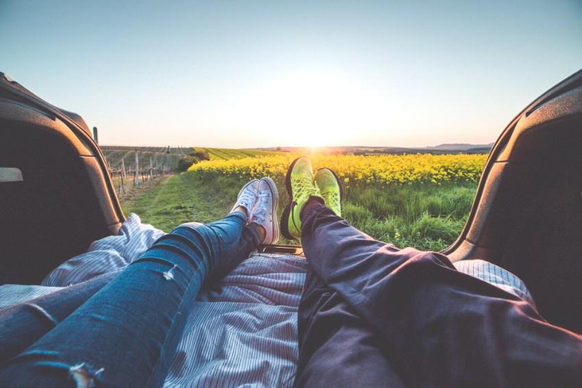 Casal junto em campo florido com sol nascendo ao fundo