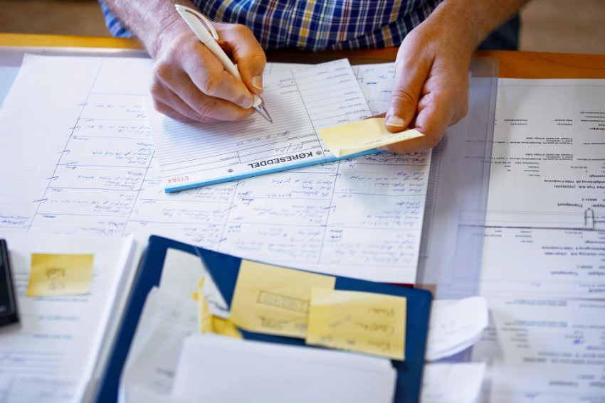 Mãos masculinas escrevendo em papel em cima de uma mesa com vários post its e papéis