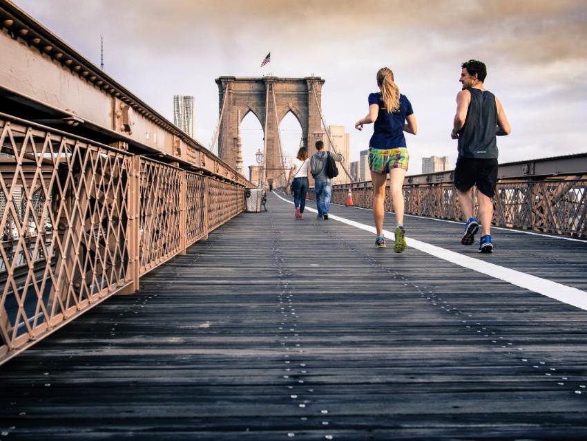 Um homem e uma mulher correm juntos em uma ponte em Londres