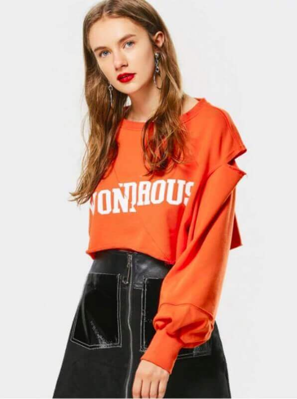 mulher com saia de couro e moletom laranja