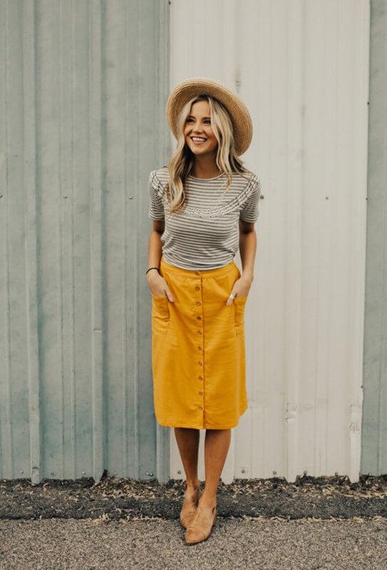 2. A saia midi com botões na frente é uma peça atemporal que não pode faltar no seu guarda-roupa -  Foto: Sra. Vaidade