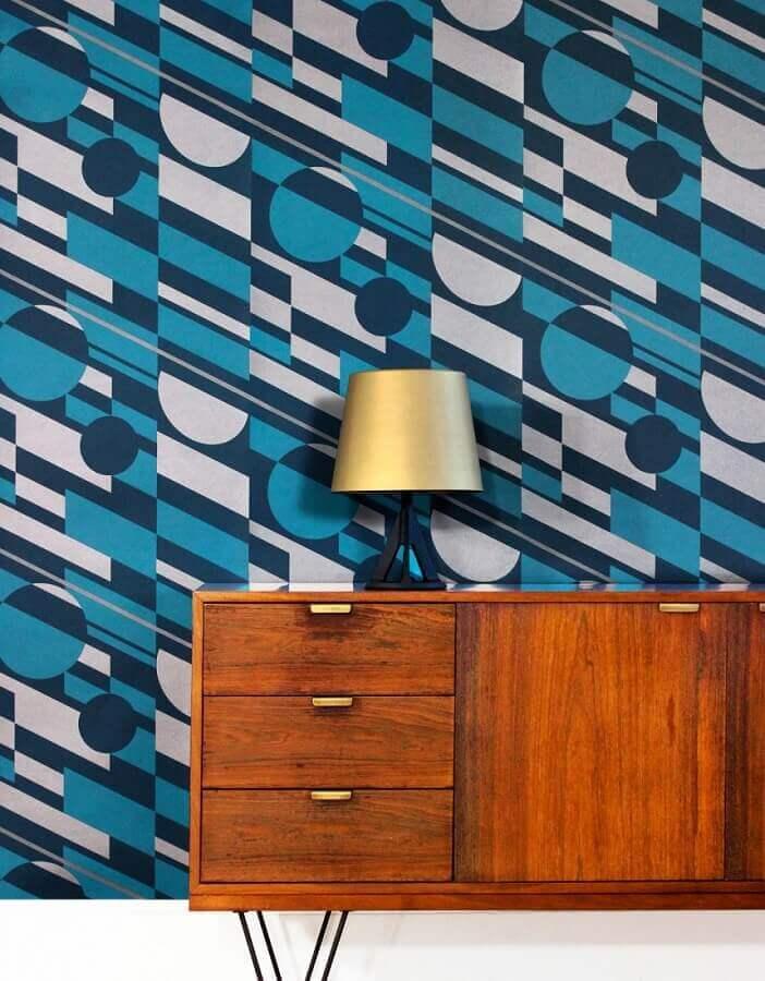 corredor decorado com aparador de madeira e papel de parede azul com estampa geométrica